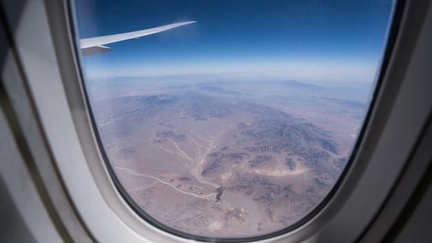 Looking thru airplane 's window seeing wing of airplane and dubai's dessert with blue sky