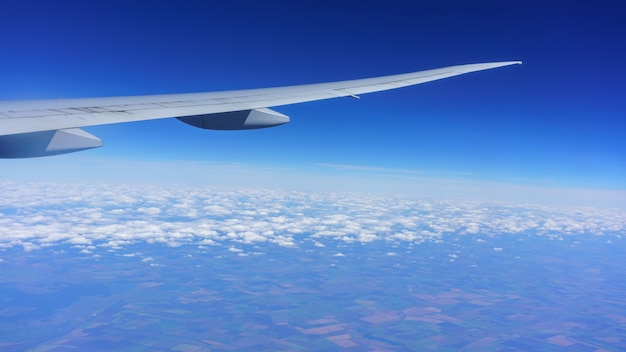 Looking thru airplane 's window seeing wing of airplane , white clouds , blue sky and land of moscow , russia
