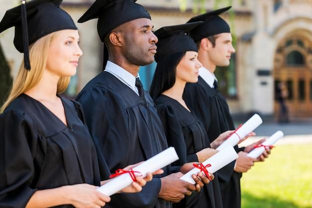 明るい未来を見据えて。卒業証書を持って、大学の前に並んで立っている間、目をそらしている4人の大学卒業生