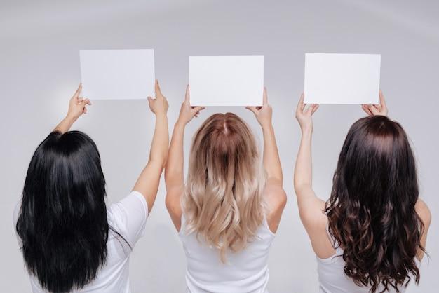 Взгляд в будущее. великолепная элегантная мощная стойка, подняв руки вверх, держа листы бумаги, вид сзади