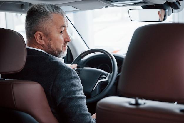 Смотря в сторону. вид сзади старшего бизнесмена в официальной одежде за рулем современного нового автомобиля