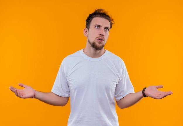 孤立したオレンジ色の背景にどのようなジェスチャーを示す白いtシャツを着ている若い男を見上げて