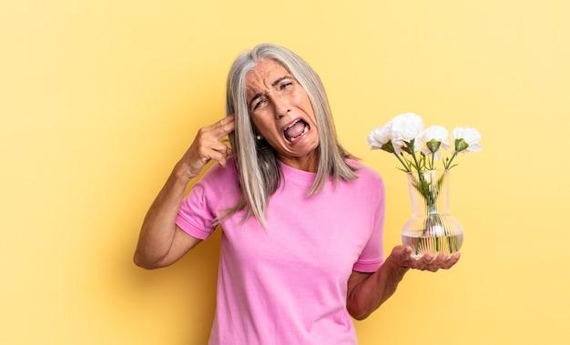 不幸でストレスを感じているように見え、装飾的な花を持っている頭を指して、手で銃のサインを作る自殺ジェスチャー