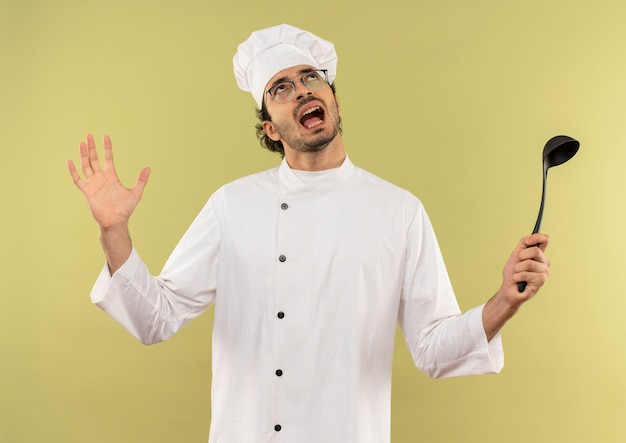 Guardando su arrabbiato giovane cuoco maschio che indossa l'uniforme del cuoco unico e bicchieri tenendo il mestolo e diffondere la mano