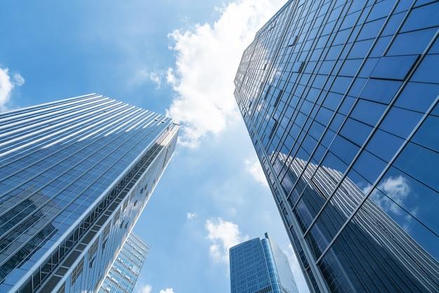 青いモダンなオフィスビルを見上げる