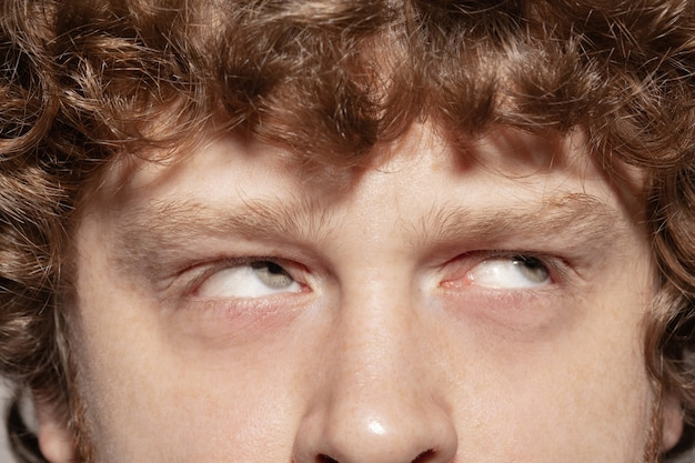 Looking up. close up of face of beautiful caucasian young man, focus on eyes.