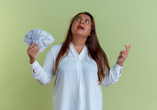 Guardando in su preoccupato casual caucasica donna di mezza età in possesso di contanti e dita incrociate