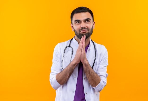 Guardando il giovane medico maschio interessato in su che indossa l'abito medico dello stetoscopio che mostra pregare il gesto su fondo giallo isolato