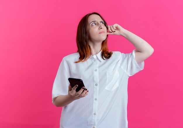 Guardando fino confuso giovane ragazza rossa che tiene il telefono e mettendo il dito sulla testa isolata su sfondo rosa