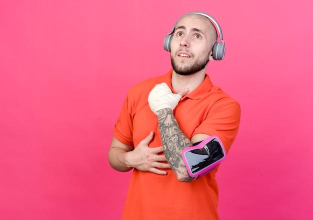 Guardando il giovane sportivo impressionato con fasciatura da polso che indossa le cuffie con fascia da braccio del telefono isolata sulla parete rosa