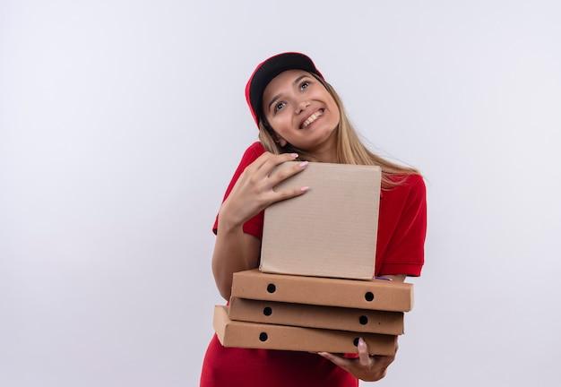 Guardando la giovane ragazza allegra di consegna che indossa l'uniforme rossa e le scatole di contenimento del cappuccio isolate su fondo bianco con lo spazio della copia