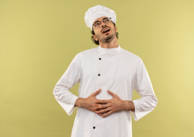 Guardando in su che ride giovane cuoco maschio che indossa l'uniforme e gli occhiali del cuoco unico afferrò lo stomaco