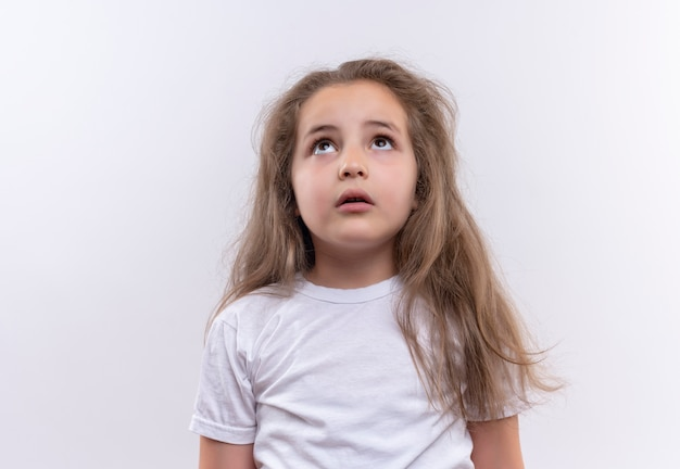 Guardando la piccola ragazza della scuola che indossa la maglietta bianca su fondo bianco isolato