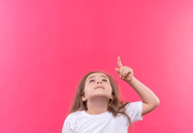 Guardando verso l'alto la piccola ragazza della scuola che indossa la maglietta bianca indica su fondo rosa isolato