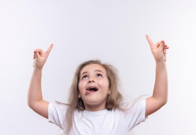Guardando la piccola ragazza della scuola che indossa la maglietta bianca indica su sfondo bianco isolato