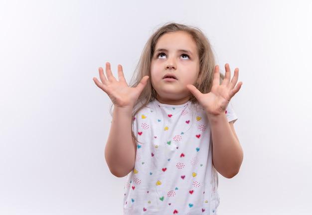 Cercando di alzare la maglietta bianca da portare della bambina della scuola che solleva le mani su fondo bianco isolato