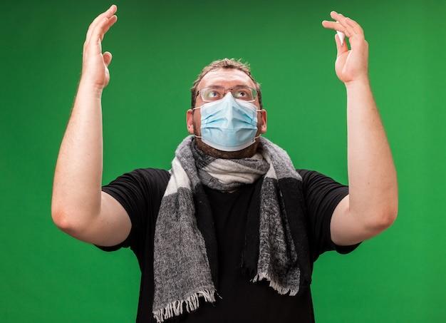 Alzando lo sguardo maschio malato di mezza età che indossa maschera medica e sciarpa alzando le mani