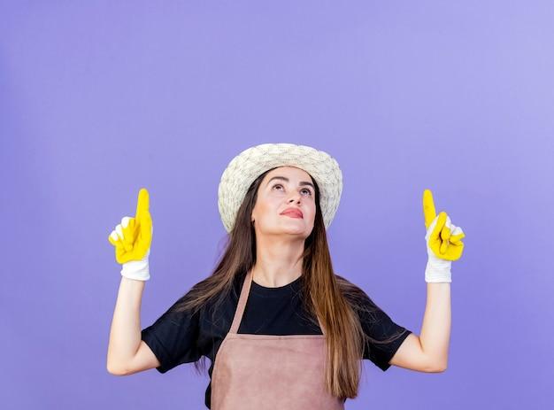 Guardando su soddisfatto bella ragazza giardiniere in uniforme indossando guanti e cappello da giardinaggio indica in alto isolato su sfondo blu con spazio di copia