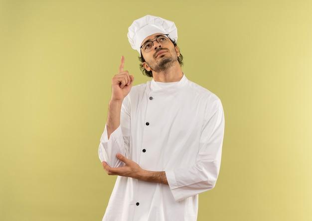Guardando il giovane cuoco maschio soddisfatto che indossa l'uniforme e gli occhiali del cuoco unico verso l'alto