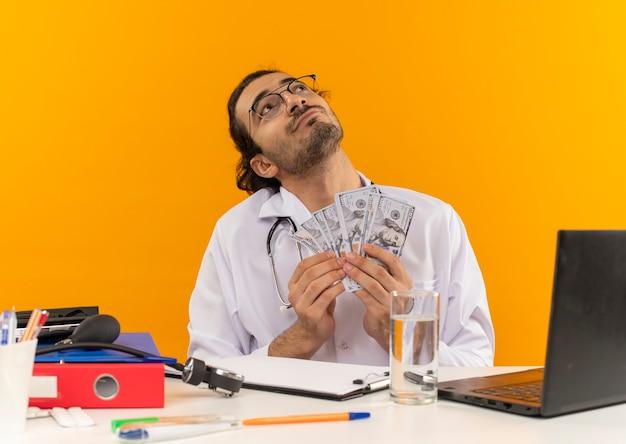 Guardando il giovane medico maschio soddisfatto con gli occhiali medici che indossano l'abito medico con lo stetoscopio seduto alla scrivania