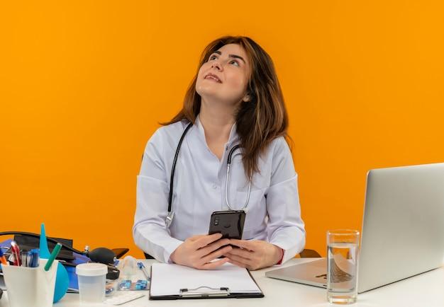 Guardando il medico femminile di mezza età sorridente che indossa la veste medica con lo stetoscopio che si siede alla scrivania lavora sul computer portatile con strumenti medici che tengono il telefono sulla parete arancione isolata con lo spazio della copia