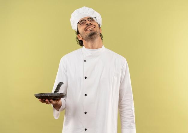 Guardando in su sorridente giovane cuoco maschio che indossa l'uniforme del cuoco unico e bicchieri tenendo la padella