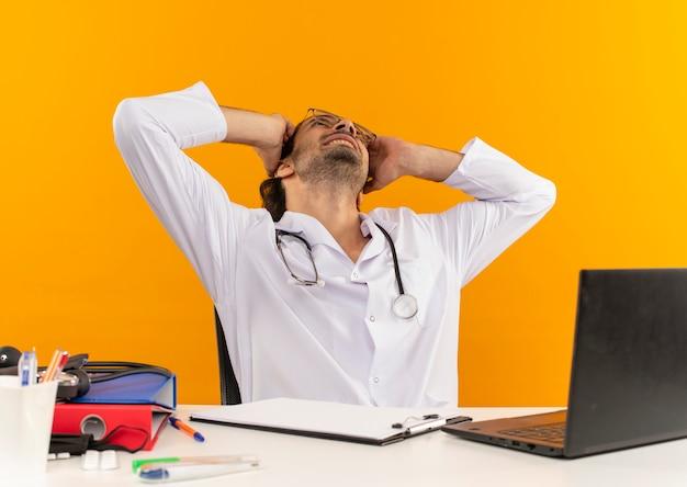 Guardando il giovane medico maschio sorridente con gli occhiali medici che indossano l'abito medico con lo stetoscopio seduto alla scrivania