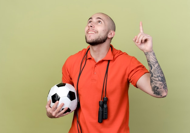 Guardando il giovane sportivo sorridente punta verso l'alto tenendo la palla con la corda per saltare sulla spalla isolato su sfondo verde oliva