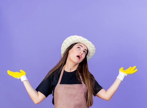 Guardando la bella ragazza del giardiniere sorpresa in uniforme che indossa il cappello da giardinaggio e guanti che diffondono le mani isolate su fondo blu con lo spazio della copia
