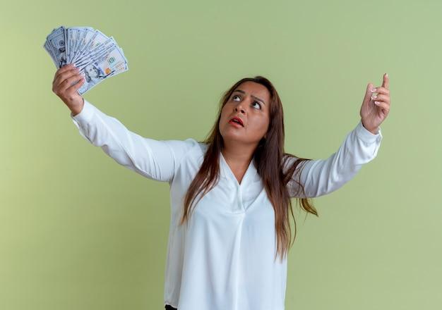 Guardando la donna di mezza età caucasica casuale sorpresa in su che tiene contanti e punti in su