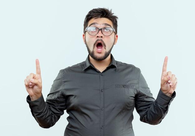 Guardando il giovane uomo d'affari sorpreso con gli occhiali indica in alto isolato su sfondo bianco con spazio di copia