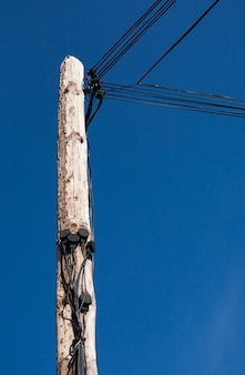 Looking up at telegraph pole with many wires
