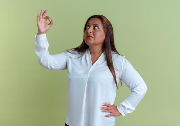 Guardando in su pensando donna di mezza età caucasica casuale che mostra il gesto okey e che mette la mano sull'anca