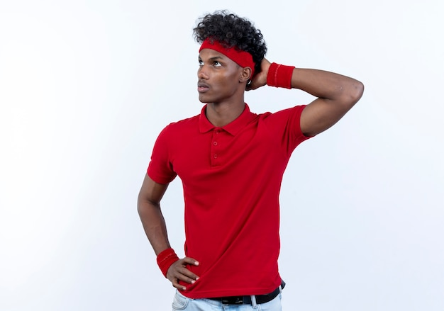Looking at up thinking young afro-american sporty man wearing headband and wristband putting hand on head isolated on white background