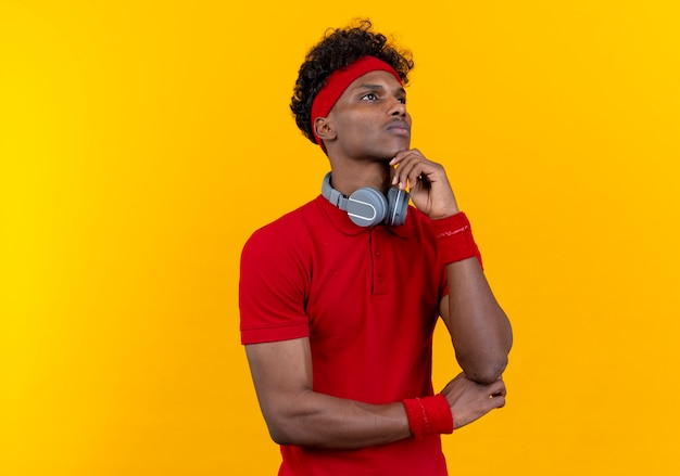 Looking at up thinking young afro-american sporty man wearing headband and wristband with headphones on shoulder putting hand under chin isolated on yellow background