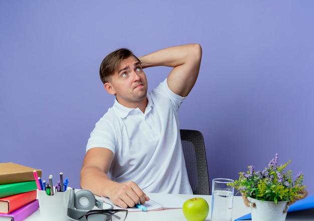 Guardando il pensiero giovane studente maschio bello seduto alla scrivania con strumenti di scuola mettendo la mano dietro la testa isolata sulla parete blu
