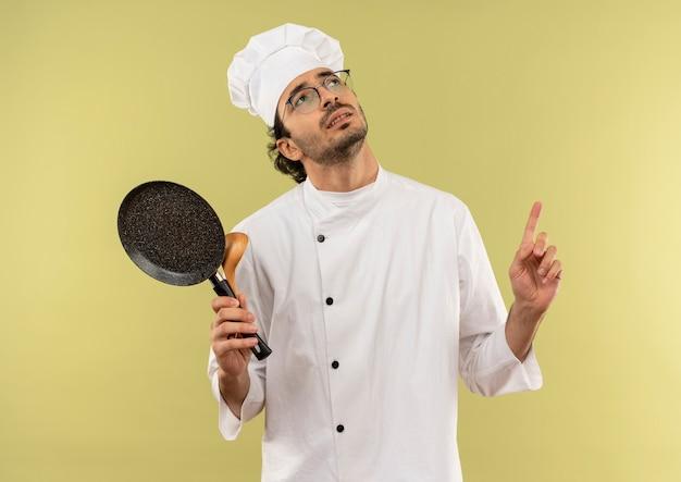 Guardando in su pensando giovane cuoco maschio che indossa l'uniforme dello chef e bicchieri tenendo la padella con il cucchiaio e punta verso l'alto