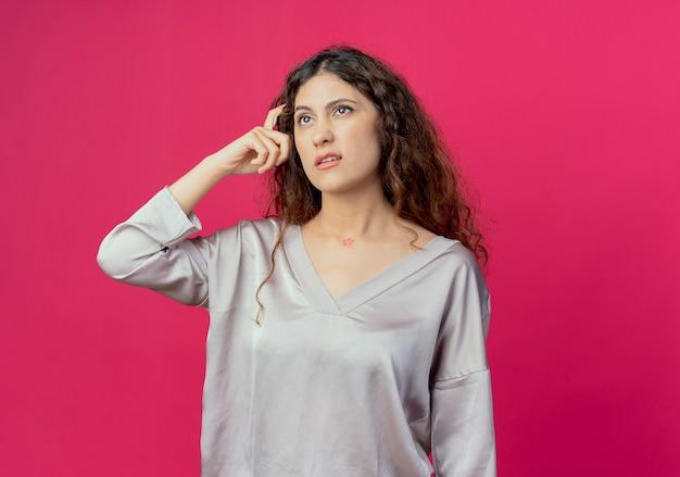 Guardando in alto pensare giovane ragazza carina graffiare la testa isolata su sfondo rosa
