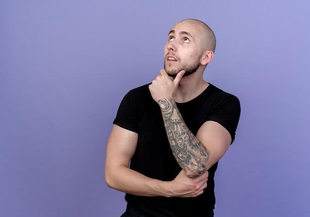 Guardando il pensiero giovane uomo sportivo mettendo la mano sul mento isolato sulla parete viola