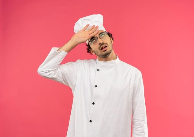 Guardando in su stanco giovane cuoco maschio che indossa l'uniforme del cuoco unico e bicchieri mettendo la mano sulla fronte