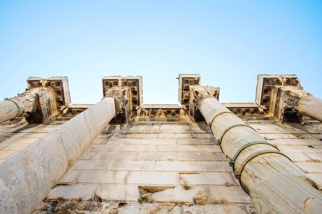 ギリシャの澄んだ青い空を背景に有名なギリシャ神殿の柱の眺めを見上げる