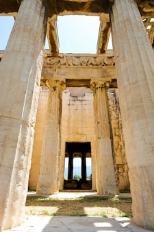Глядя вверх вид на колонны знаменитого греческого храма на фоне ясного голубого неба в греции