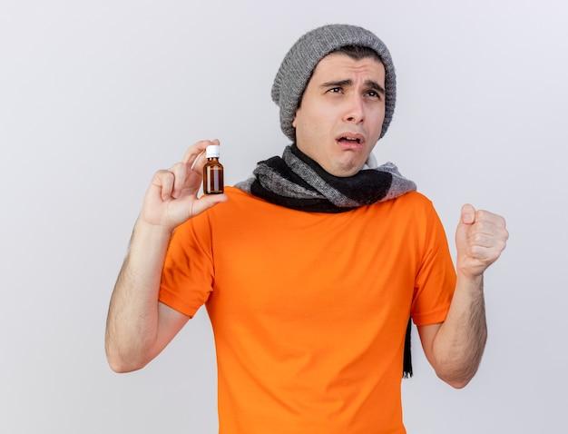 Guardando il debole giovane uomo malato che indossa il cappello invernale con sciarpa tenendo la medicina in bottiglia di vetro