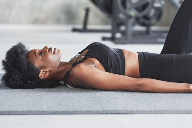 Looking up when lying down on the floor and taking a break, african american woman with curly hair and in sportive clothes have fitness day in the gym