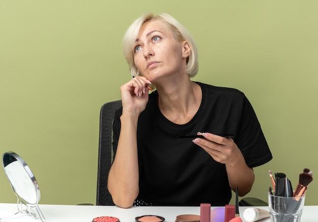 Alzando lo sguardo la giovane bella ragazza si siede al tavolo con gli strumenti per il trucco tenendo il pennello per il trucco isolato sul muro verde oliva