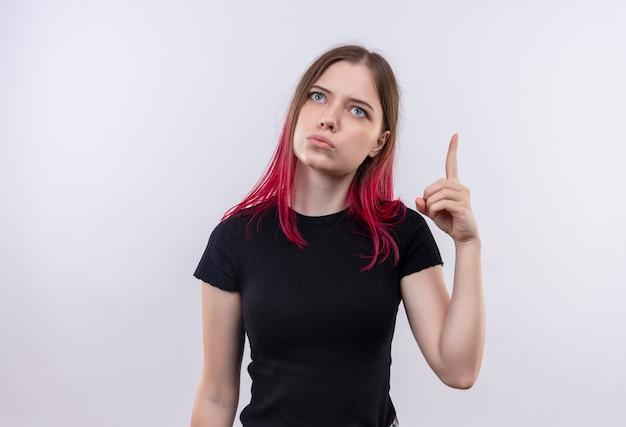 Guardando la giovane bella ragazza che indossa la maglietta nera punta il dito su sfondo bianco isolato