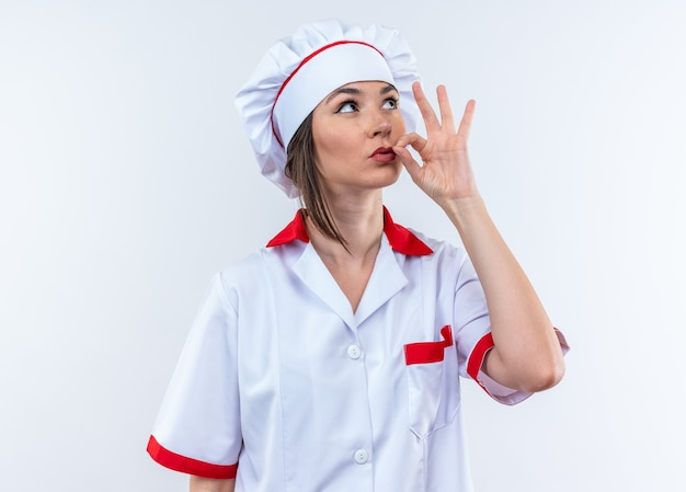 Cercando giovane cuoca che indossa l'uniforme dello chef che mostra un gesto delizioso isolato su parete bianca