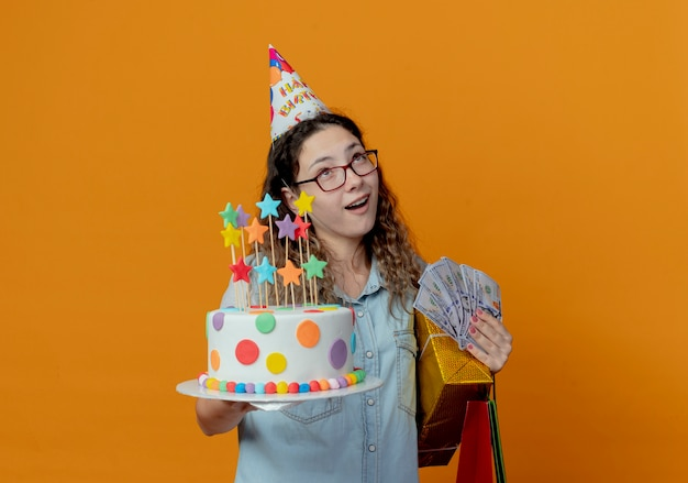 Looking at up young girl wearing glasses and birthday cap holding birthday cake with gift bags with boxes and money isolated on orange background