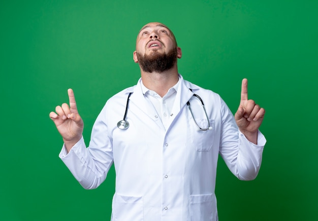 Looking at up young male doctor wearing medical robe and stethoscope points at up