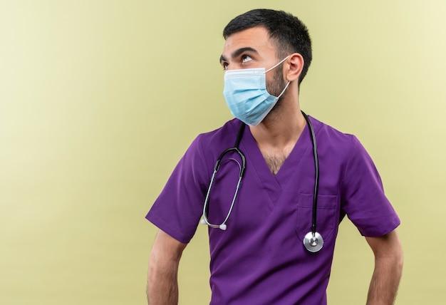 Guardando il giovane medico maschio che indossa abiti chirurgo viola e maschera medica stetoscopio su sfondo verde isolato